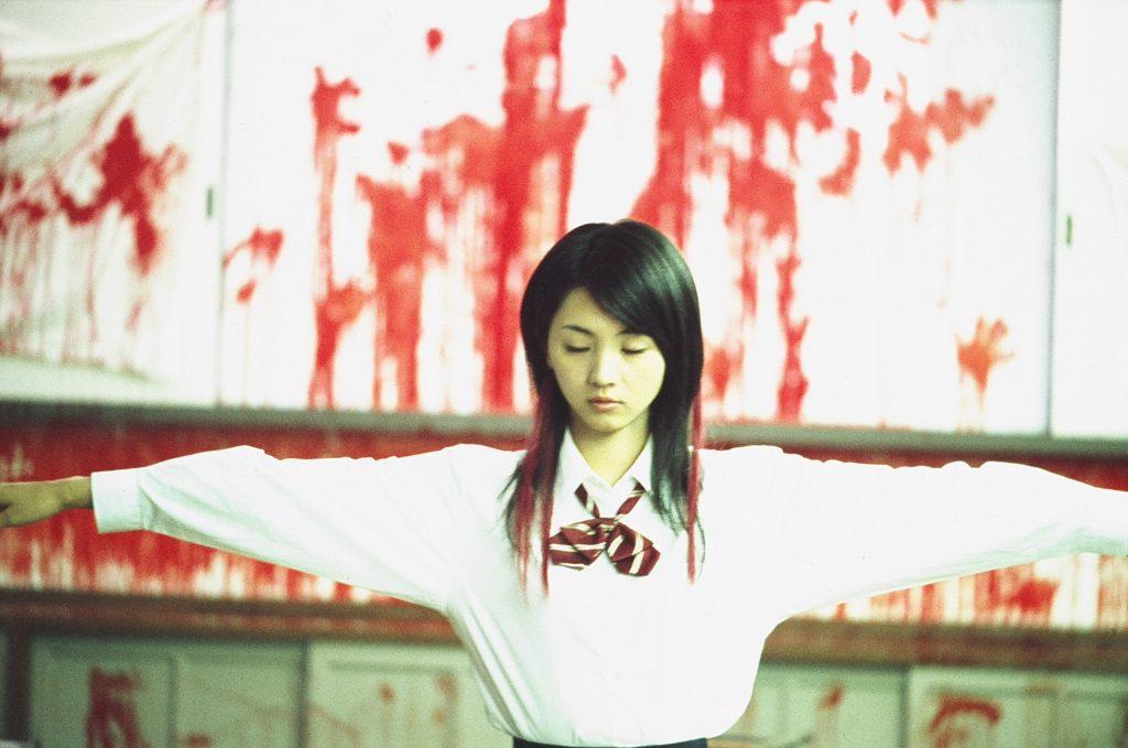 Yu steht mit ausgestreckten Armen vor einer blutbeschmierten Wand.