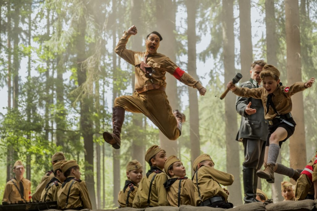 Jojo springt gemeinsam mit seinem imaginären Hitler und einer Granate in der Hand an der Hitlerjugend vorbei