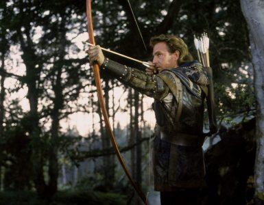 Kevin Costner als Robin Hood zielt mit gespanntem Bogen