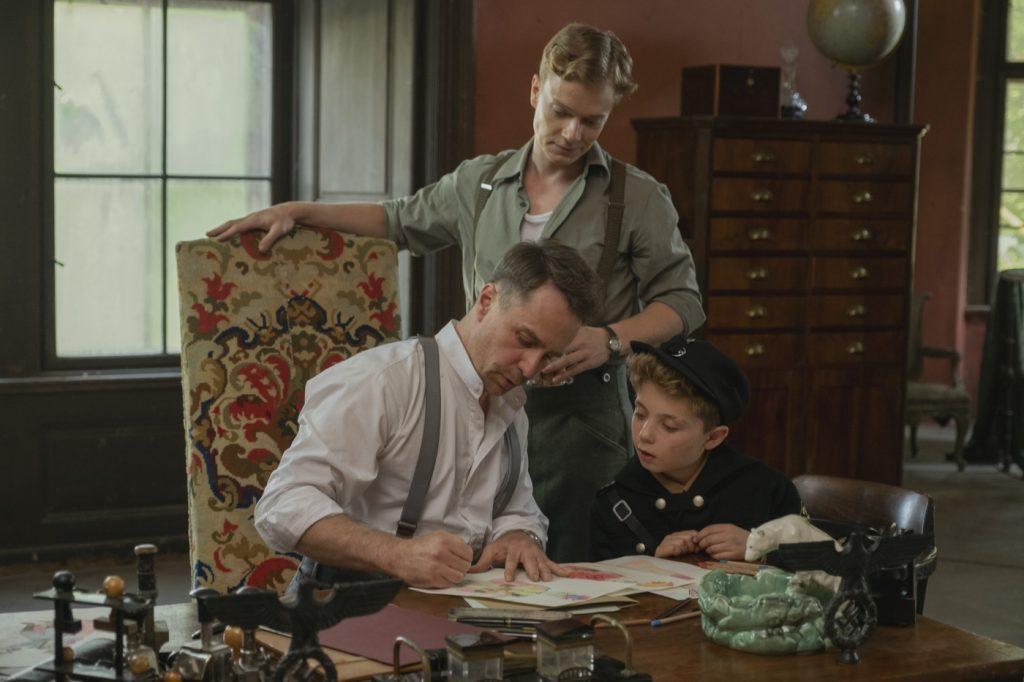 Captain Klenzendorf (Sam Rockwell) zeigt Jojo (Roman Griffin Davis) und Finkel (Alfie Ellen) sein Uniform-Design