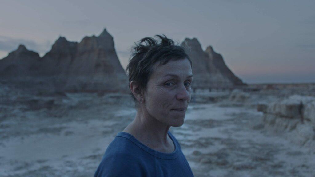 Frances McDormand als Hauptfigur Fern schaut mit kurzen windzerzausten Haaren in die Kamera, hinter ihr weites unbebautes Land