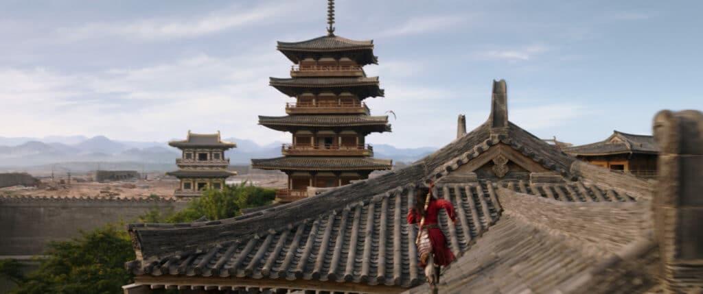 Hua Mulan (Liu Yifei) läuft in ihrem roten Gewand grazil und sicher über die Dächer von traditionellen chinesischen Gebäuden.