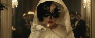 Cruella, im weißen Gewand und mit schwarzer Maske, betritt die Gesellschaft