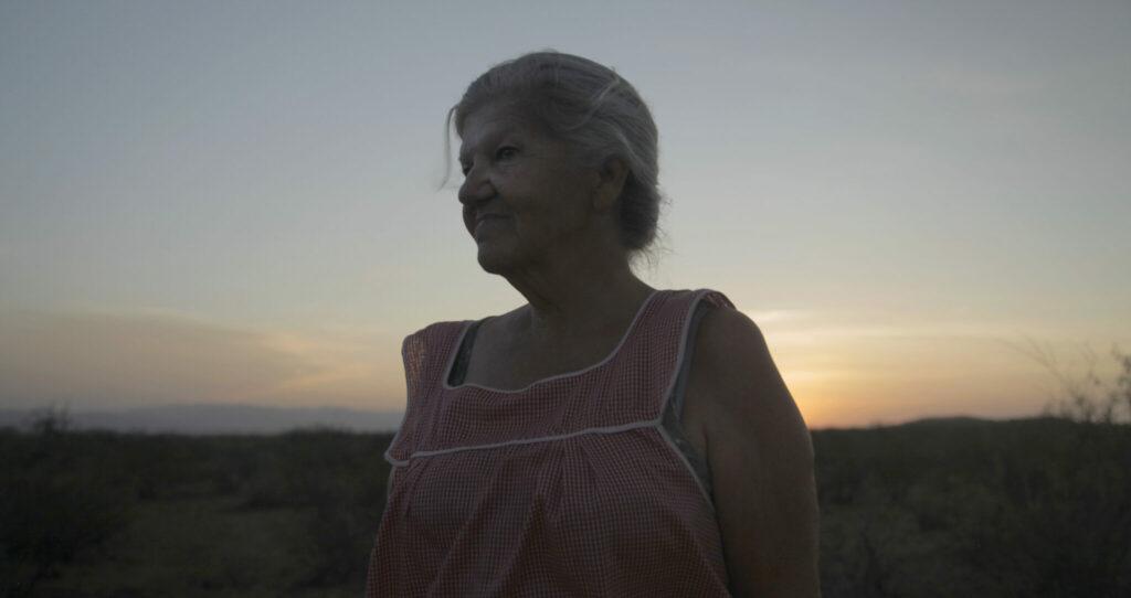 Laiendarstellerin Linda May im Halbdunkeln mit Sonnenuntergang im Hintergrund