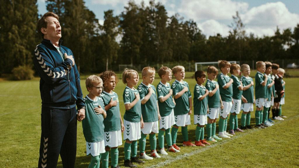Tommy und seine Fußballmannschaft stehen in Reih und Glied auf dem Rasen und singen die Nationalhymne.