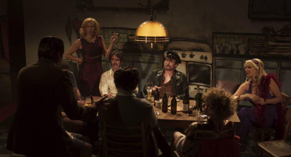 """Rainer Werner Fassbinder und sein """"Klan"""" sitzen gemeinsam in der Küche und besprechen ihren nächsten Film. Die Kulisse ist wie in einem Theaterstück aufgemalt."""