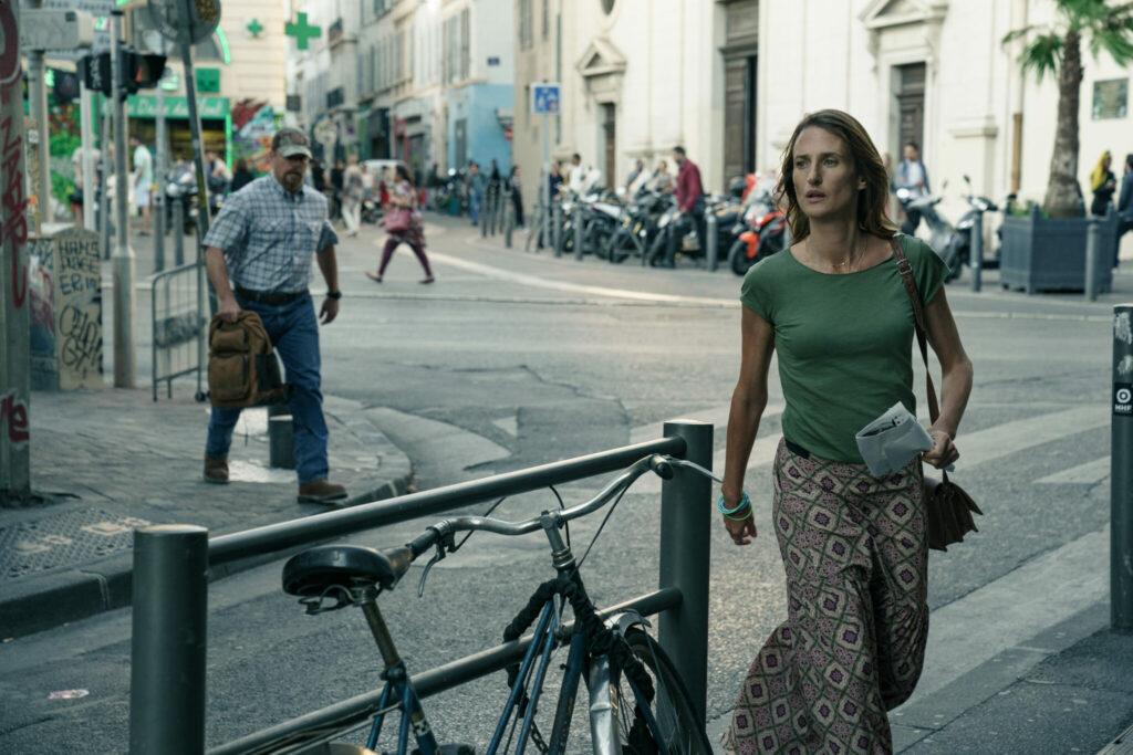 Camille Cottin schaut suchend den Gehweg entlang, Matt Damon folgt ihr über die Straße - Stillwater