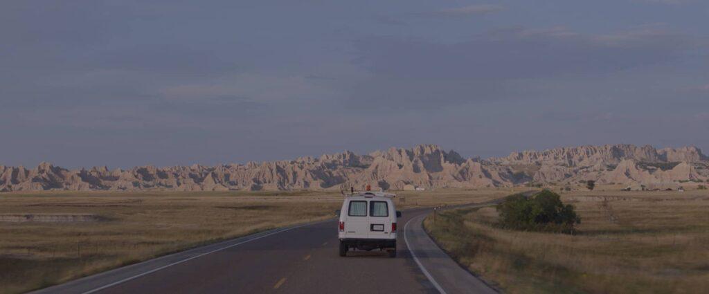 Ein weißer Van fährt auf einer einsamen Straße im unbebauten Land