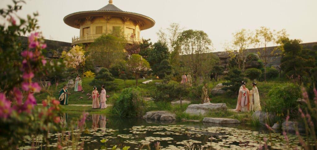 Mulan (2020) hat eindrucksvolle Kulissen. Wie hier einen kleinen, von vielseitigen und wohl gepflegten Gewächsen umrundeten, See vor einem historischen Gebäude.