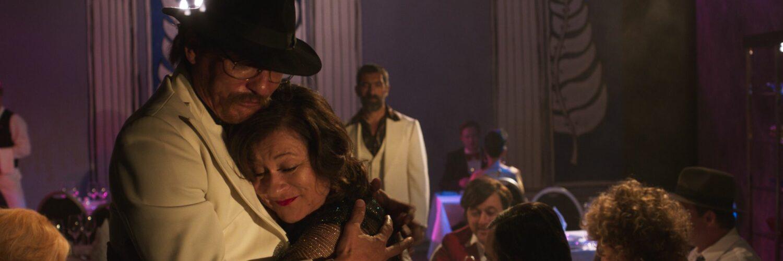 Rainer Werner Fassbinder und Brigitte Mira umarmen sich in Enfant Terrible glücklich, während El Hedi ben Salem aus der Ferne zuschaut.