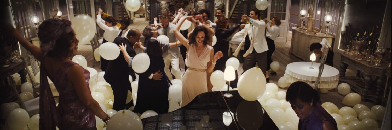 Eine Ballszene aus Tod auf dem Nil. Zahlreiche Personen tanzen vor einem schwarzen Flügel. Um sie herum liegen und fliegen weiße Ballons.