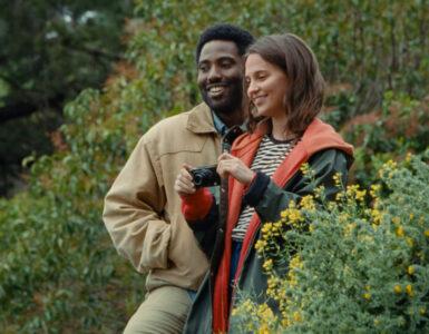 Beckett (John David Washington) und April (Alicia Vikander) stehen in der Natur, während ihres Urlaubs in Griechenland. Es sind einige Pflanzen und Büsche um sie herum zu erkennen. April hält eine Kamera in beiden Händen. Beide lächeln glücklich.