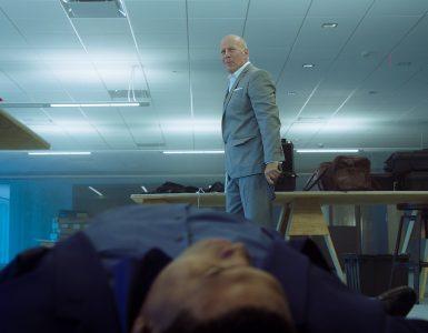 Bruce Willis steht als Rex mit der Waffe in der Hand vor einem auf dem Boden liegenden, toten Kompagnon in 10 Minutes Gone