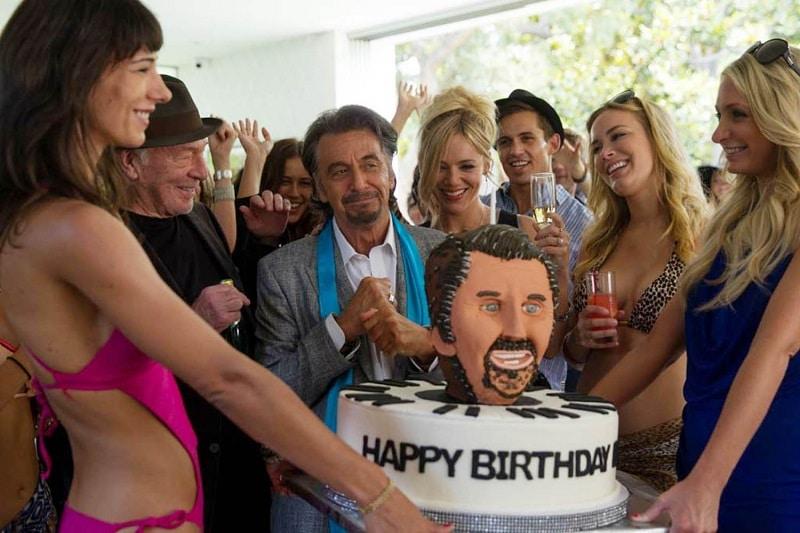 Danny steht mit seinem Manager und einigen hübschen Models vor einer großen Geburtstagstorte, die sein grinsendes Antlitz ziert - Mr. Collins' zweiter Frühling