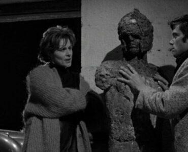Künstlerin Vivica Lindfors lehnt locker an die Mauer und redet auf Rocker Oliver Reed ein, der Hand an ihre unfertige Skulptur legt - Hammer Horrorfilme.