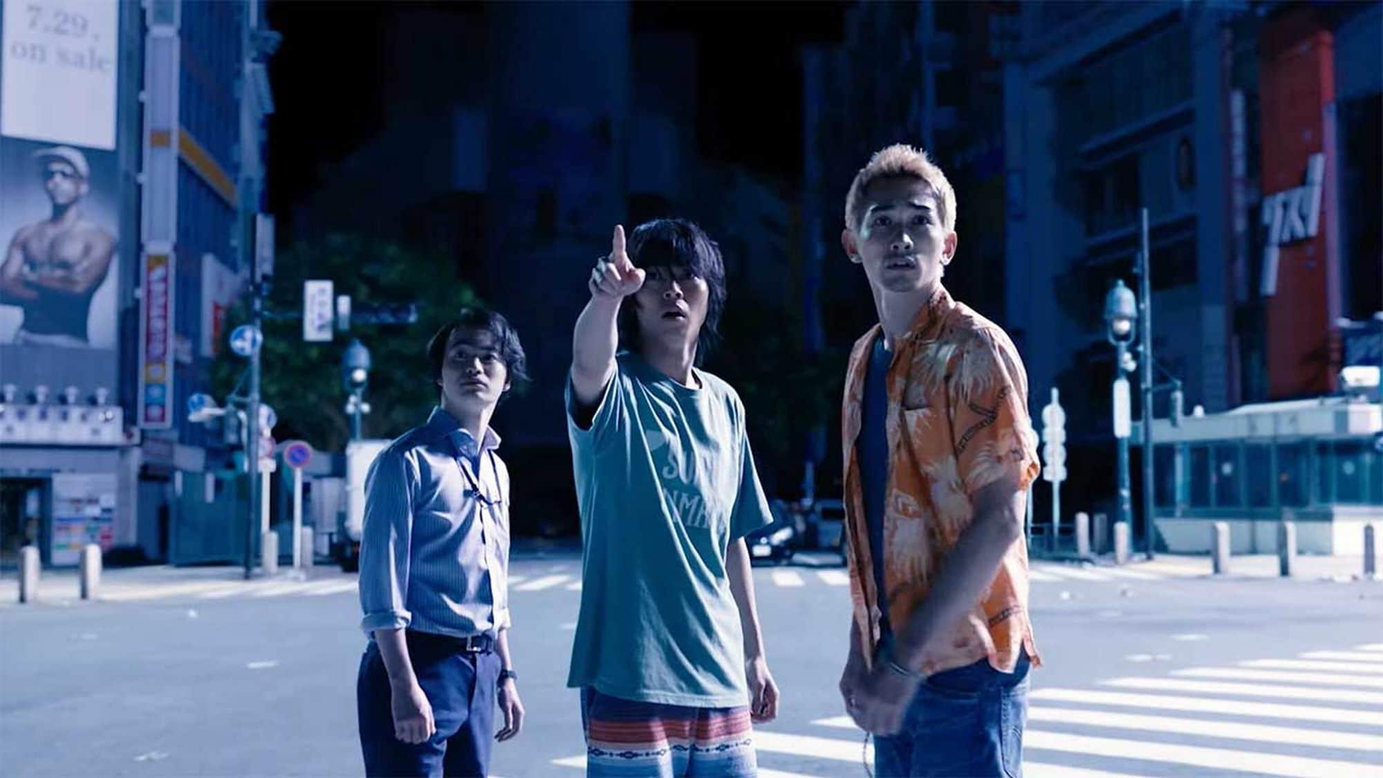 Arisu, Karube und Chota stehen nachts inmitten einer menschenleeren Kreuzung. Im Hintergrund sieht man Hochhäuser und einen Ubahneingang.