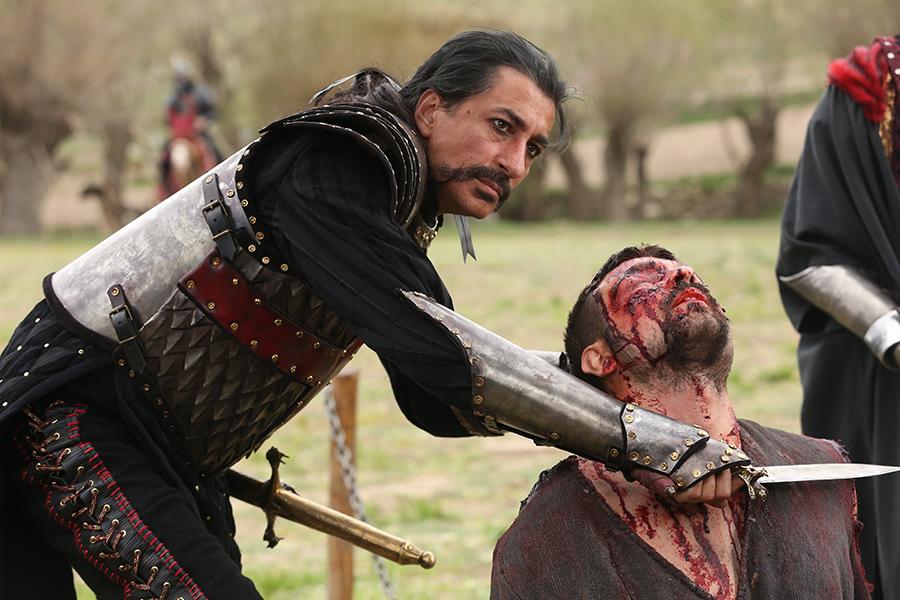 Vlad III. hält einem blutüberströmten Mann, der neben ihm kniet, ein Messer an die Kehle, Deliler - Sieben für die Gerechtigkeit