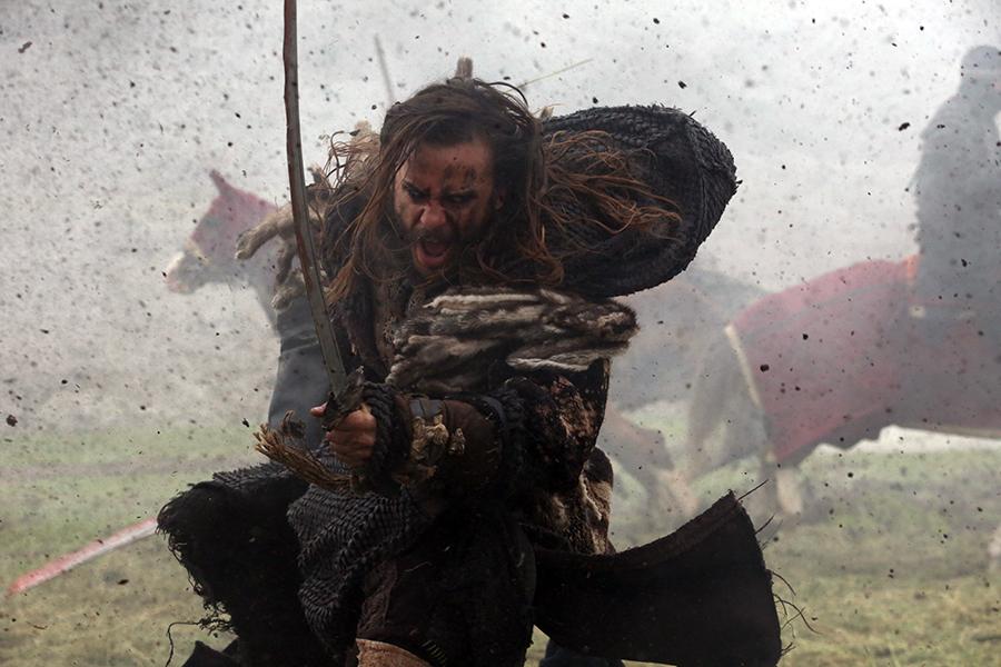 Suskun rennt schreiend in den Kampf, während um ihn herum Erde aufwirbelt