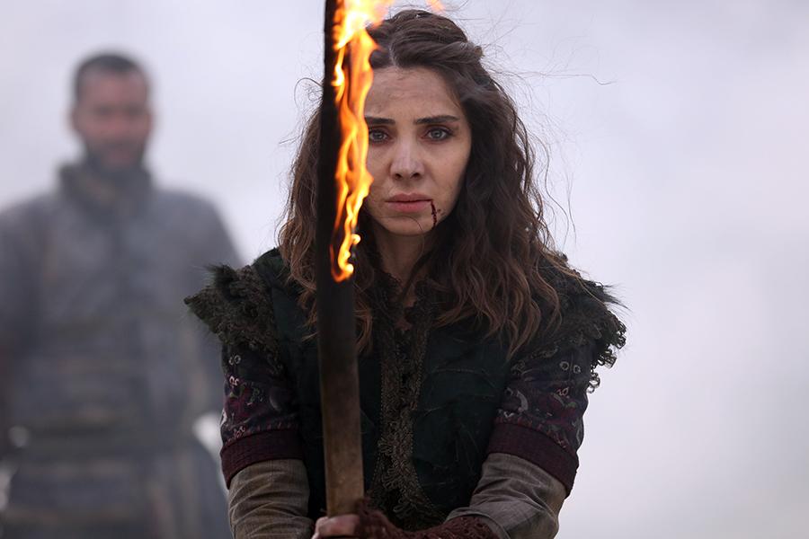Alaca steht mit einem brennenden Stück Holz einer Gruppe Plünderern gegenüber