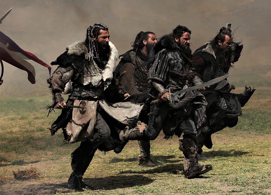 Vier Deliler rennen brüllend über ein Schlachtfeld