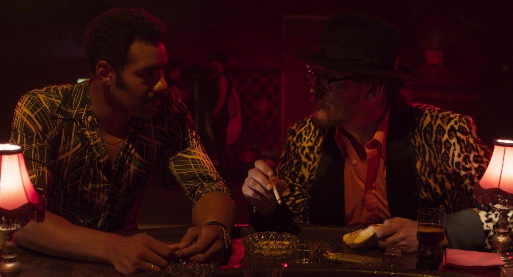 Fassbinder (rechts) redet mit seinem Liebhaber Günther Kaufmann (links) in einer Bar, während Fassbinder seine blutige Nase verheilt und eine Zigarette in der Hand hält. Eine Szene aus dem Film Enfant Terrible.