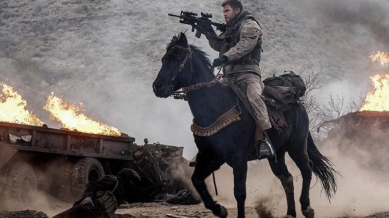 Chris Helmsworth zielt in 12 Strong mit seiner MP, fest im Sattel seines Pferdes - Neu auf Netflix im Mai 2020