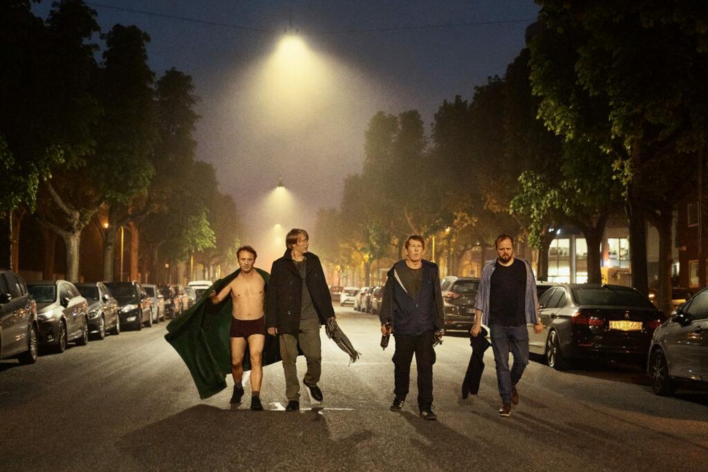 Die vier Freunde Peter, Martin, Nikolaj und Tommy torkeln nachts betrunken in der Mitte einer Straße in Der Rausch