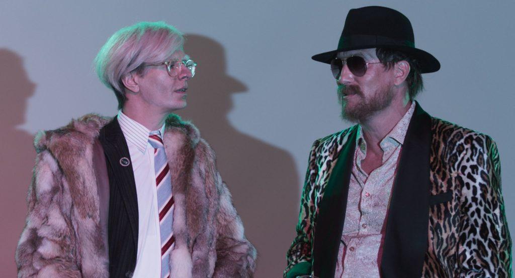 Der Enfant Terrible Rainer Werner Fassbinder (Oliver Masucci) trifft Andy Warhol (Alexander Scheer). In Sachen extravaganter Kleidung schenken sich die beiden nichts.