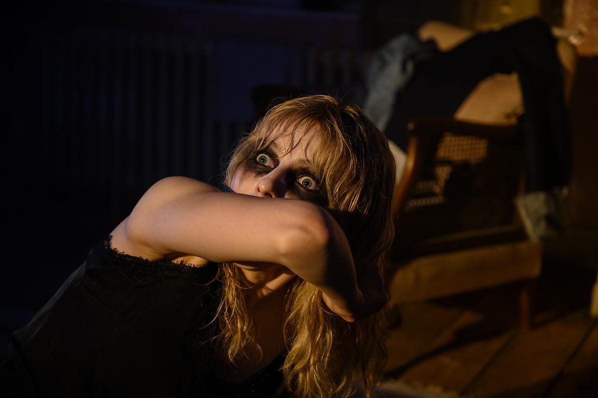 Thomasin McKenzie in Last Night in Soho mit dunkel geschminkten Augen und erschrockenem Blick. Sie hält sich den Arm vors Gesicht