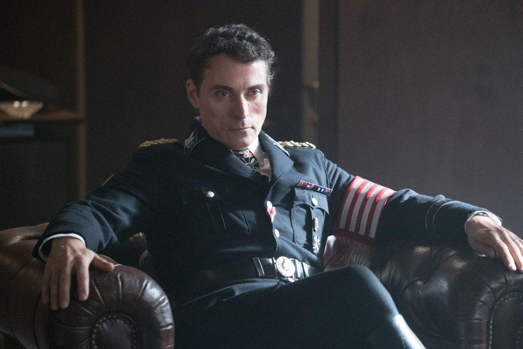 Nazi-Kommandant mit amerikanischer Flagge am linken Arm in einem Sessel, lächelt bedrohlich