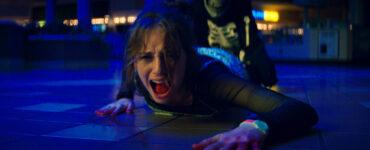 Maya Hawke als Heather in Fear Street Teil 1. Sie liegt schreiend auf dem Boden und wird von hinten am Bein gehalten