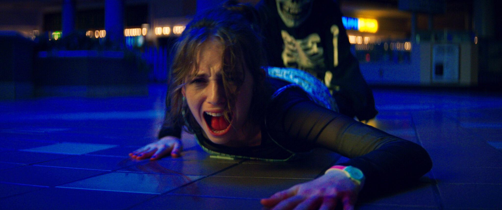 Maya Hawke liegt schreiend auf dem Boden in einem dunklen Raum und schreit vor Angst. Hinter ihr sieht man jemanden angedeutet, der sie an den Beinen festhält.