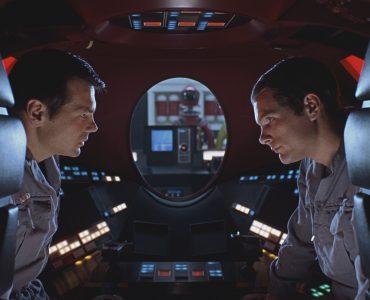 Poole (Gary Lockwood) und Bowman (Keir Dullea) unterhalten sich mit ernstem Ton in einer Raumkapsel über ihr Vorgehen. Im Hintergrund ist durch ein Fenster Super-Computer HAL 9000 zu sehen.