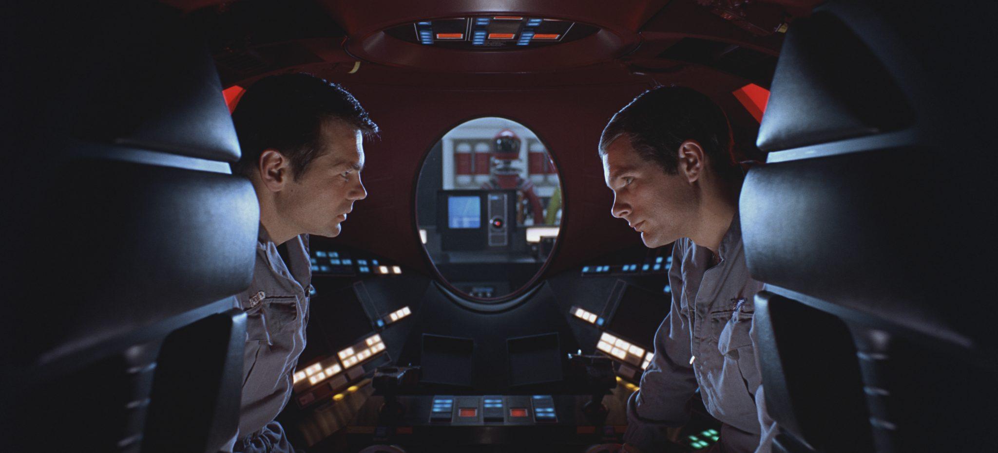 """Poole (Gary Lockwood) und Bowman (Keir Dullea) unterhalten sich in dieser Szene aus """"2001"""", einem der berühmtesten Filmer der 60er, mit ernstem Ton in einer Raumkapsel über ihr Vorgehen. Im Hintergrund ist durch ein Fenster Super-Computer HAL 9000 zu sehen."""