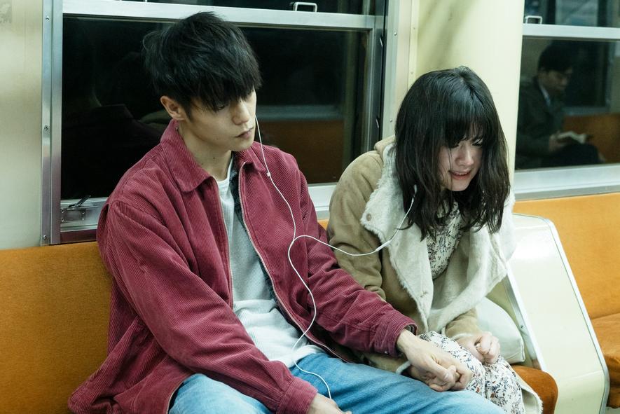 Leo und Monica sitzen auf einer Bank in einem U-Bahn Abteil. Leo hält Monicas Hand in First Love, einem der besprochenen japanaischen Filme.