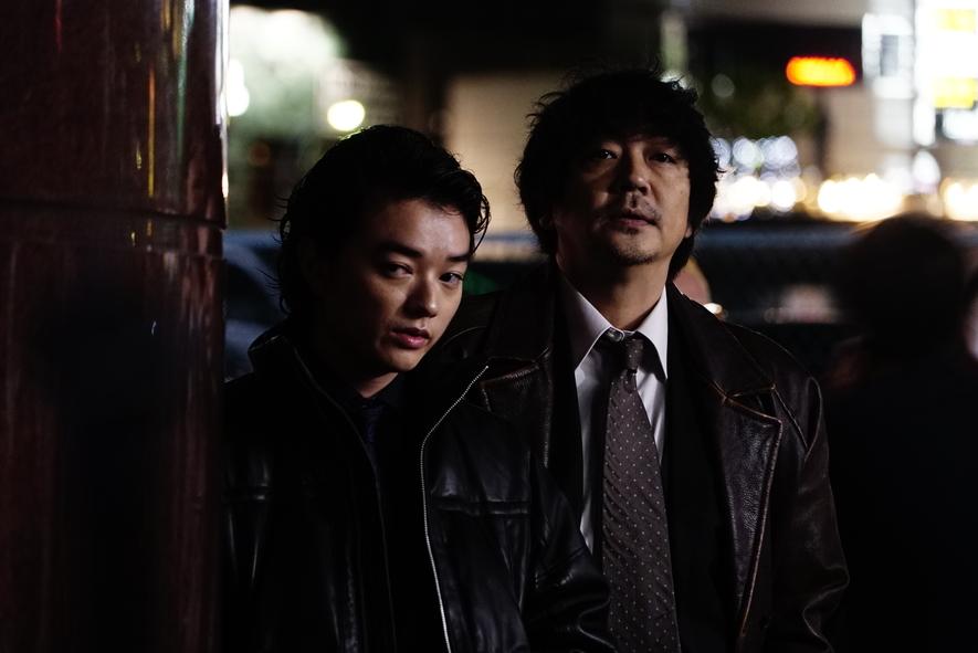 Kase und Otomo betrachten das Geschehen gespannt von einer Straßenecke aus.