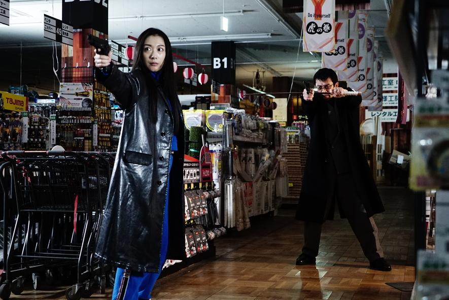 Chiachi und Ichikawa stehen in einem Gang im Supermarkt, haben ihre Waffen gezückt in First Love.