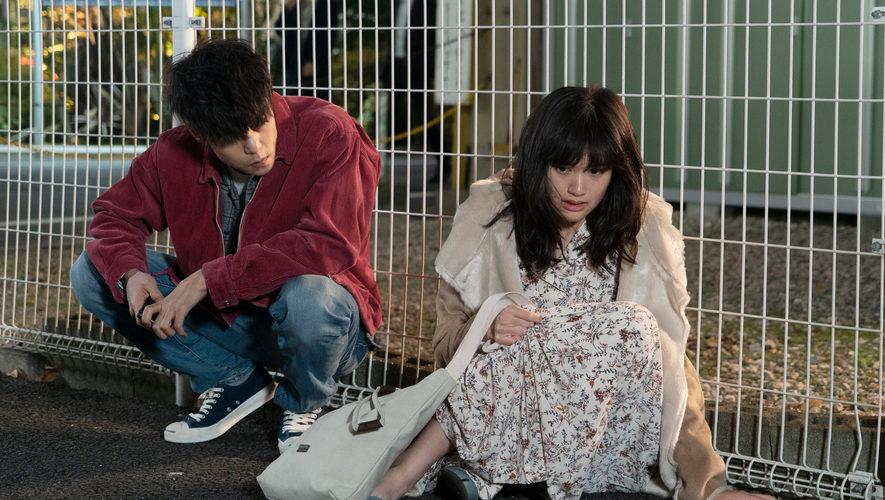 Leo und Monica hocken vor einem Gitterzaun erschöpft am Boden in First Love