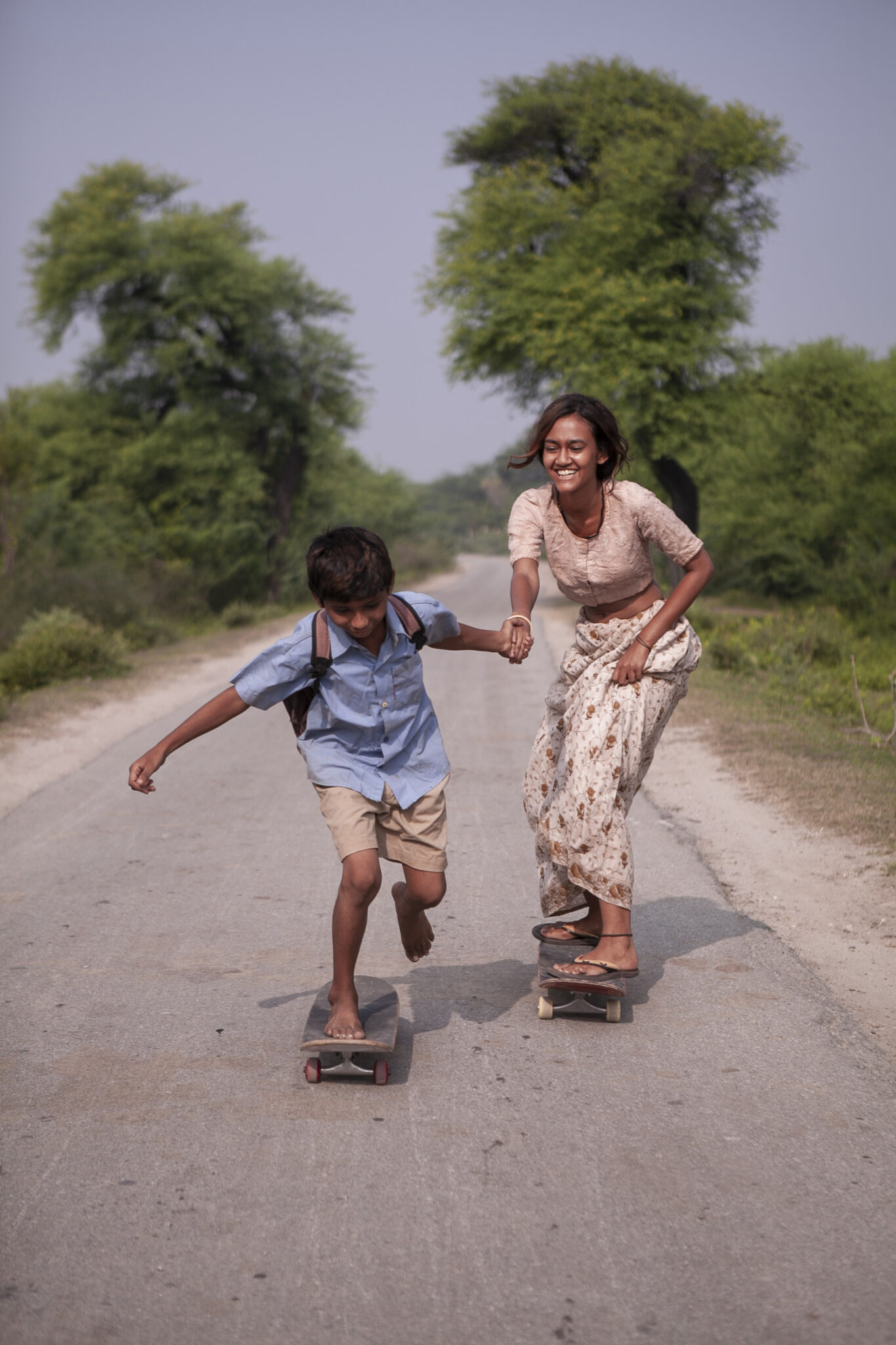 Ankush und Prerna fahren mit ihren Skateboard zusammen auf einer Landstraße. Sie trägt ein helles Shit und einen langen Rock, er hat ein blaues Hemd und eine kurze, braune Hose an.