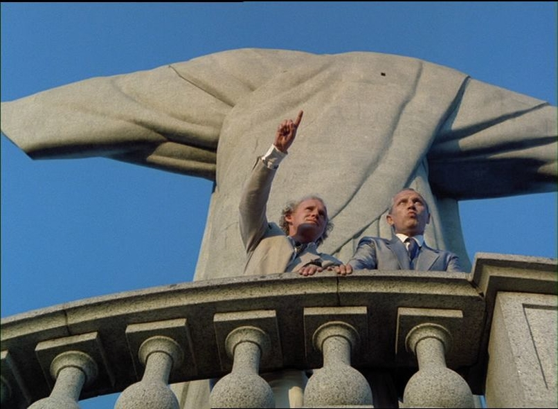 """Clive Ingram und Jack McFarland stehen vor der Rückseite von """"Christus, dem Erlöser"""" und Ingram zeigt auf etwas in der Ferne, Gefangen in Rio ©Splendid Film"""