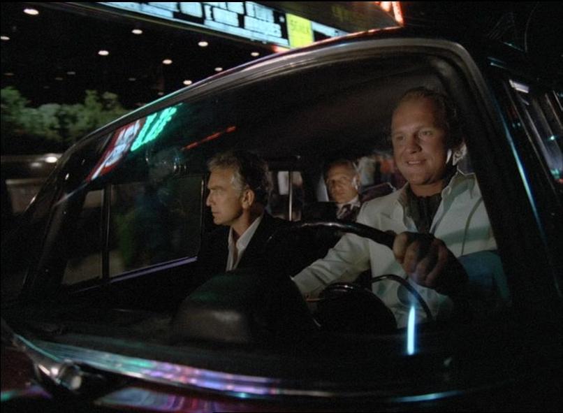 Ronald Biggs, Jack McFarland und Clive Ingram sitzen im Auto und fahren nachts vor einem Geschäft vorbei, Gefangen in Rio ©Splendid Film