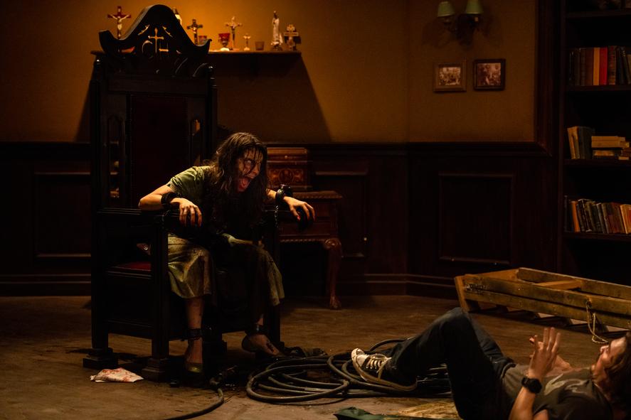 Die in Exorzismus 2.0 von einem Dämon besessene Frau sitzt angefesselt auf einem Stuhl und sorgt dennoch für reichlich ärger