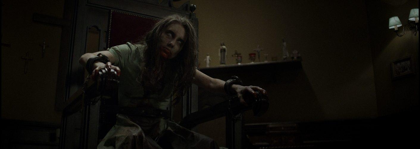 Exorzismus 2.0 zeigt eine Frau, die an einem Stuhl gefesselt ist und vom Dämon besessen ist.