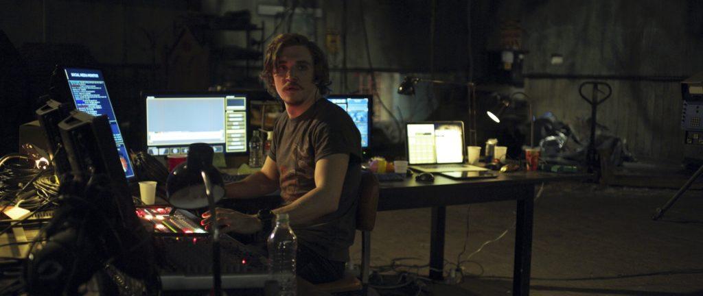 Drew (Kyle Gallner) zieht die Fäden der Show im Hintergrund und beobachtet das Geschehen von seinem mit Monitoren überfüllten Schreibtisch aus.