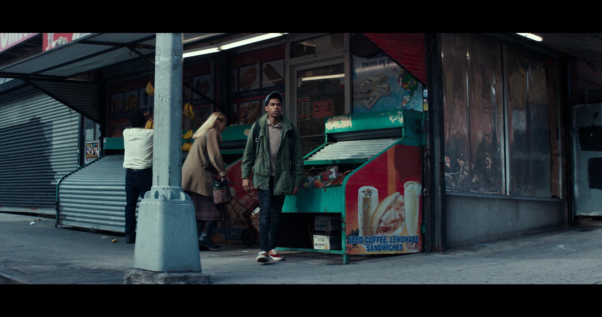 Steve kommt aus einem kleinen Laden während hinter ihm eine blonde Frau Richtung Eingang geht. Im Vordergrund steht ein Laternenpfahl. Steve trägt einen grünen Parka, eine Basecap und eine dunkle Jeans.
