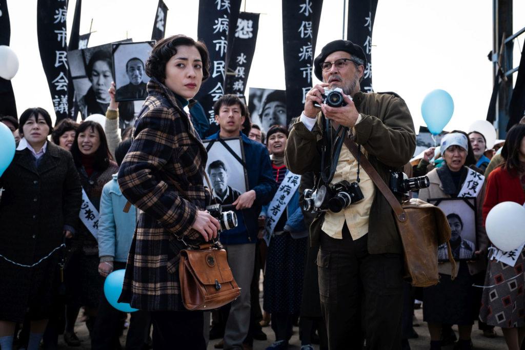 Mitsuo (Minami) und Smith (Johnny Depp) stehen mit ihren Kameras in den Änden vor einer Menschenmasse in Minamata