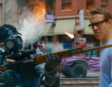 Ryan Reynolds schreitet in Free Guy verwundert über die mit aus allen Rohren feuernden Gestalten bevölkerte Straße - Neu auf Sky im Oktober 2021