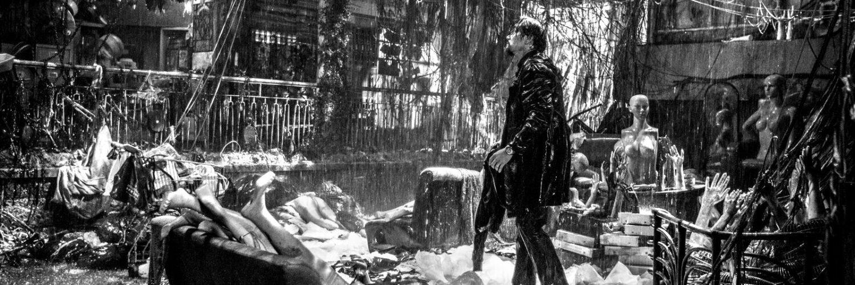 Cham Lau steht in Limbo in einem zerstörten Zimmer, wo zahlreiche wahllose Gegenstände herumliegen.