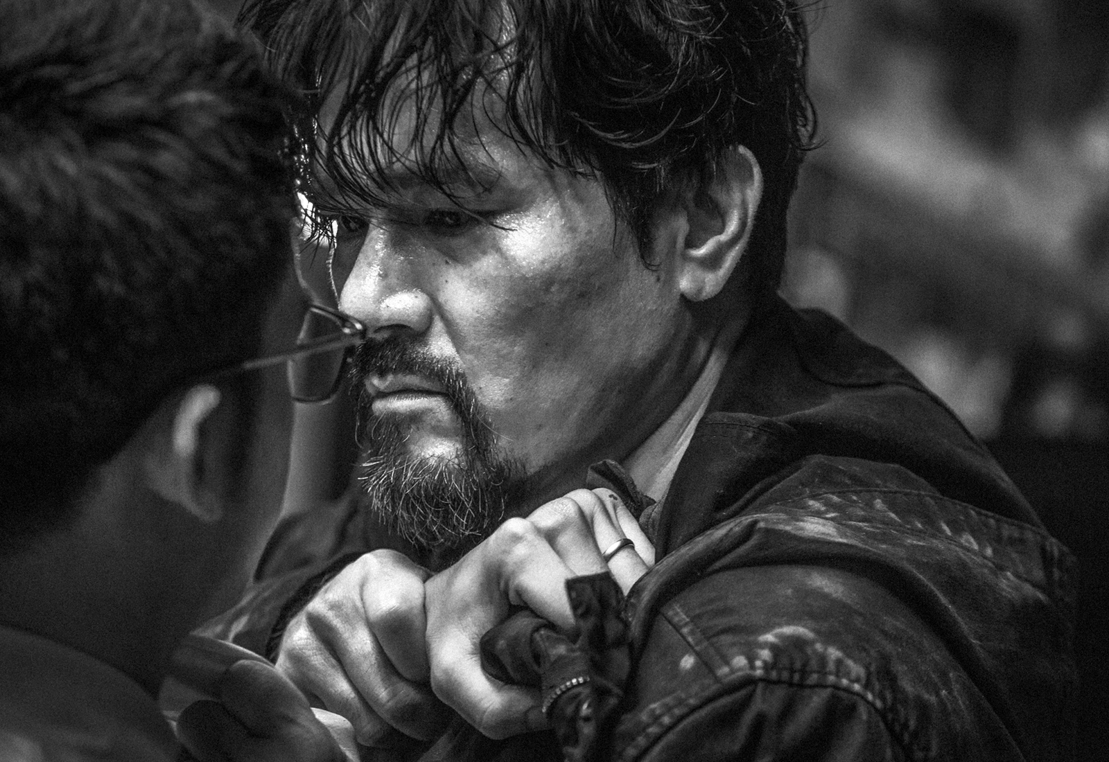 Cham Lau (Ka Tung Lam) versucht mit seiner Hand die seines Gegenüber von seiner Jacke zu entfernen. Er trägt eine schwarze Jacke und blickt mit leeren Augen drein. Von hinten erkennt man den Hinterkopf von Will Ren mit Brille.