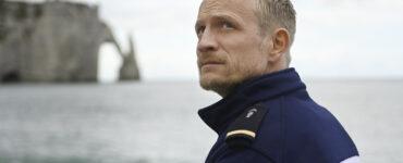Jérémie Renier steht in Uniform am Strand und schaut besorgt nach oben - Albatros